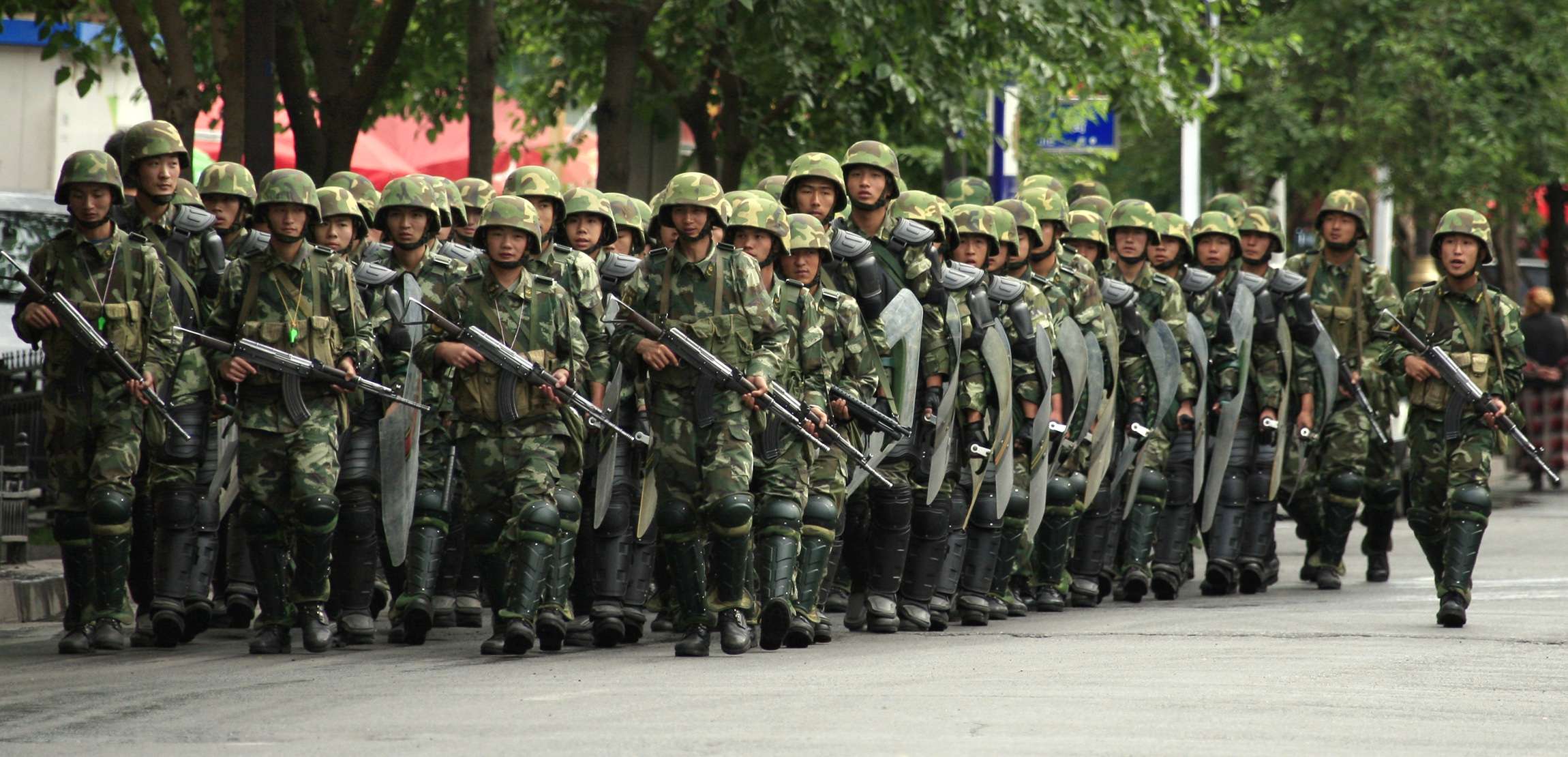 Armed Chinese paramilitary police in riot gear march along main near Dong Kuruk Bridge mosque in Urumqi in China's Xinjiang Autonomous Region